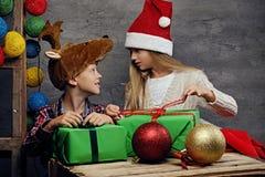 Adolescente y una muchacha en el sombrero del ` s de Papá Noel que presenta con las cajas de regalo Fotos de archivo libres de regalías