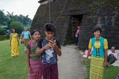Adolescentes acima tradicionalmente vestidos e bettler velho na frente de uma entrada do templo imagens de stock royalty free