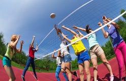 Adolescentes activos que juegan a voleibol en corte del juego Imágenes de archivo libres de regalías