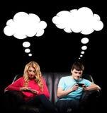 Adolescentes adictos de la tecnología en un sofá Imagen de archivo