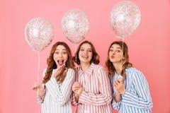 Adolescentes adorables 20s en los pijamas rayados coloridos que presentan encendido Fotografía de archivo