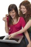 Adolescentes afortunados con la computadora portátil Fotos de archivo libres de regalías