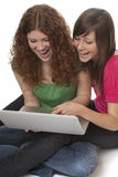 Adolescentes afortunados con la computadora portátil Imagenes de archivo