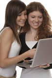 Adolescentes afortunados con la computadora portátil Fotografía de archivo