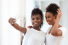 Adolescentes afro-americanos que tomam uma imagem do selfie com uma manutenção programada Imagens de Stock Royalty Free