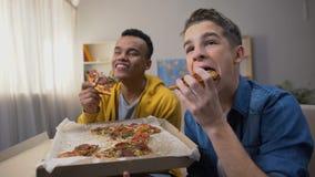 Adolescentes afroamericanos y caucásicos que gozan de la pizza y que miran a la comedia almacen de metraje de vídeo