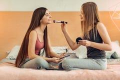Adolescentes agradables que entrenan en la aplicación de maquillaje Fotografía de archivo libre de regalías