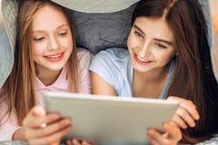 Adolescentes agradables que miran película en cama Fotografía de archivo