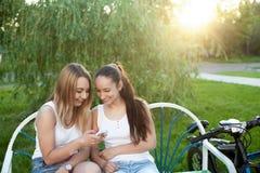 Adolescentes alegres con el teléfono móvil en parque Fotografía de archivo