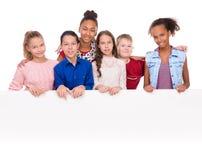 Adolescentes alegres con los pulgares que detienen un espacio en blanco vacío Fotografía de archivo libre de regalías