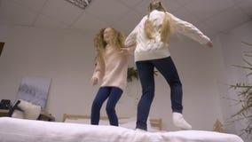 Adolescentes alegres de la muchacha que se divierten en dormitorio y que saltan en la cámara lenta de la cama i almacen de video