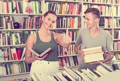 Adolescentes alegres de la muchacha y del muchacho que muestran los pulgares para arriba Imagenes de archivo