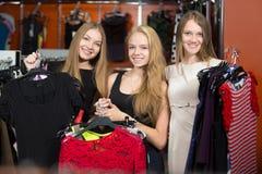 Adolescentes alegres que eligen los vestidos en la tienda Foto de archivo