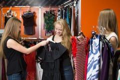 Adolescentes alegres que intentan los vestidos Imagen de archivo libre de regalías