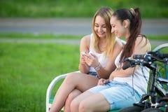 Adolescentes alegres que juegan con el teléfono móvil en banco Foto de archivo