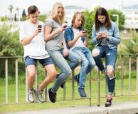 Adolescentes alegres que juegan con los teléfonos móviles Foto de archivo libre de regalías