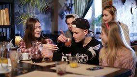 Adolescentes alegres que relaxam na cafetaria vídeos de arquivo