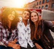 Adolescentes alegres que toman el selfie en el triciclo Imagen de archivo libre de regalías