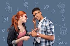 Adolescentes amistosos que se sienten bien mientras que escucha la música y el baile Foto de archivo