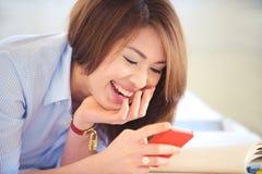 Adolescentes asiáticos hermosos colocan sonrisa con el pH móvil Foto de archivo libre de regalías
