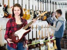 Adolescentes atractivos del muchacho y de la muchacha que examinan las guitarras eléctricas Foto de archivo libre de regalías