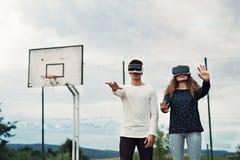 Adolescentes atractivos en patio con los vidrios de VR Foto de archivo libre de regalías
