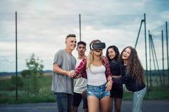 Adolescentes atractivos en patio Muchacha con los vidrios de VR Imagenes de archivo