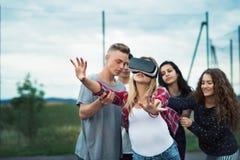 Adolescentes atractivos en patio Muchacha con los vidrios de VR Foto de archivo libre de regalías