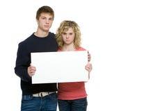 Adolescentes atractivos que llevan a cabo la muestra en blanco Fotografía de archivo