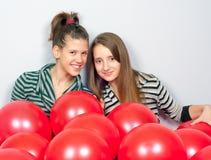 Adolescentes avec beaucoup de ballons rouges Image libre de droits
