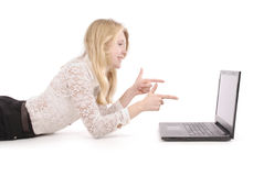 Adolescentes bastante jovenes con el ordenador portátil que miente en el piso Imagen de archivo