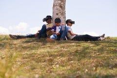 Adolescentes blancos y negros que juegan realidad virtual en parque Foto de archivo