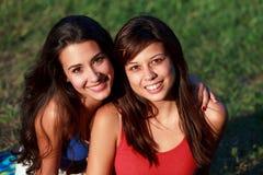 Adolescentes bonitos de la universidad que disfrutan de vida del campus Imagen de archivo libre de regalías