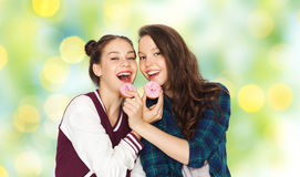 Adolescentes bonitos felices que comen los anillos de espuma Imagen de archivo