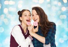 Adolescentes bonitos felices que comen los anillos de espuma Imágenes de archivo libres de regalías