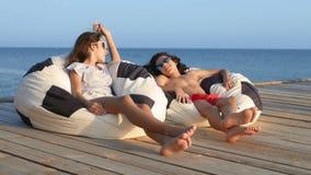 Adolescentes bonitos menino e menina que sentam-se em uma cadeira do saco em um terraço de madeira sobre o mar Falam alegremente  filme