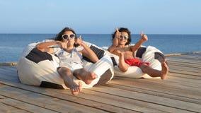 Adolescentes bonitos menino e menina que sentam-se em uma cadeira do saco em um terraço de madeira sobre o mar polegares da mostr filme