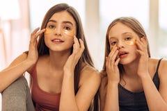 Adolescentes bonitos que aplican remiendos del debajo-ojo Foto de archivo