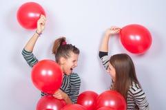 Adolescentes bonitos que juegan con los globos Imagenes de archivo