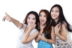 Adolescentes bonitos que señalan el espacio de la copia Imagen de archivo libre de regalías