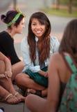 Adolescentes bonitos que se sientan en la tierra Foto de archivo