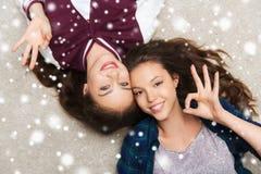Adolescentes bonitos sonrientes felices que mienten en piso Fotos de archivo libres de regalías