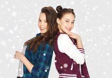 Adolescentes bonitos sonrientes felices sobre nieve Imagen de archivo libre de regalías