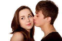 Adolescentes cariñosos de los pares. Muchacho que besa a una muchacha. Fotografía de archivo