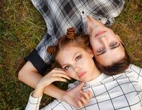 Adolescentes cariñosos de los pares que mienten en césped Fotos de archivo libres de regalías