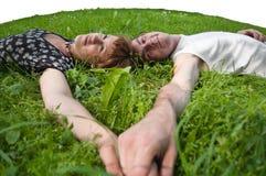 Adolescentes cariñosos jovenes de los pares que ponen en gras verdes Imagen de archivo