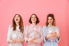 Adolescentes caucasianos 20s nos pijamas listrados coloridos que levantam o Fotos de Stock
