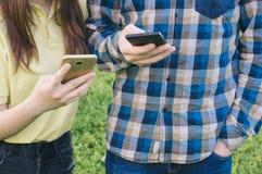 Adolescentes chating en línea Estudiantes que sostienen los teléfonos móviles Fotografía de archivo