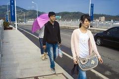 Adolescentes chinos que caminan a lo largo del camino imagen de archivo