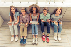 Adolescentes com dispositivos Imagens de Stock Royalty Free